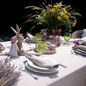 An Easter outdoors table setting with two stuffed bunnies as decor.