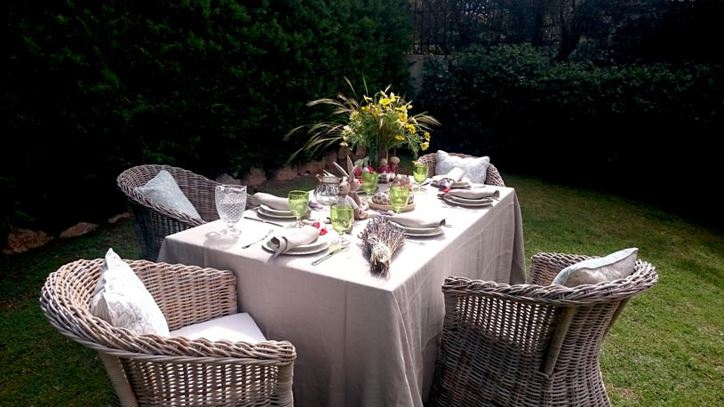 A dining table with a linen tablecloth setup in a garden. At the one corner of the table a glass vase with a wabi-sabi flower arrangement looks terrific with the rest of the greenery.