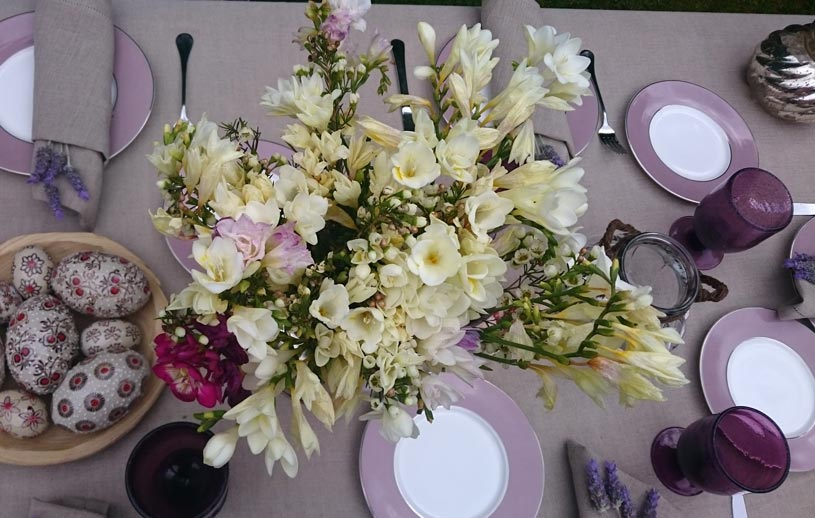 A second tablescape for Easter dining with splashes of pink and mauve accents. Close up view from atop.