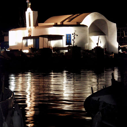 A night time view of a chapel in Naoussa Paros, lit up and reflecting onto the sea.