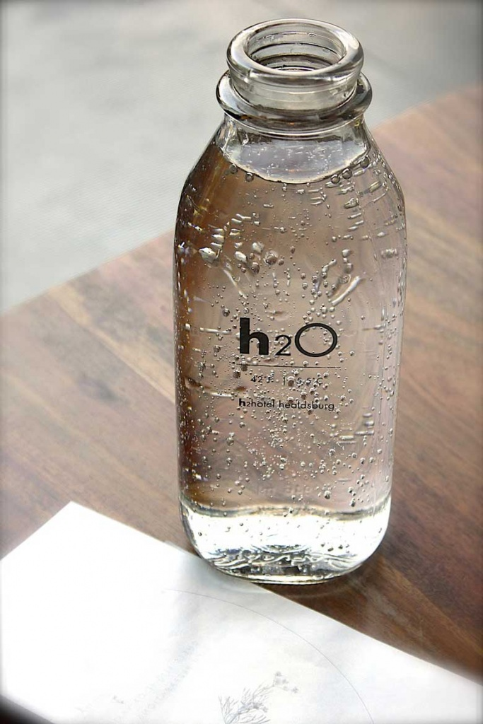 A glass bottle of water with an H2O label.