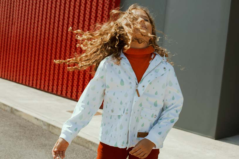 A young girl with long hair seems to be enjoying her day out in her raincoat with a raindrop print pattern.