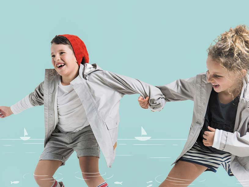 These two kids (boy and girl) seem to be having fun playing while wearing casual wear and raincoats.