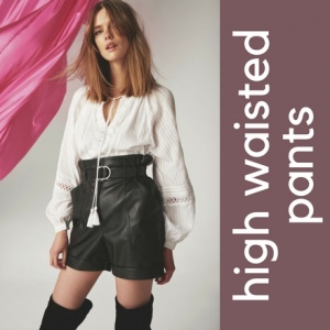 A young model wearing high waisted black faux leather shorts, knee high boots and a white shirt. Image by River Island.