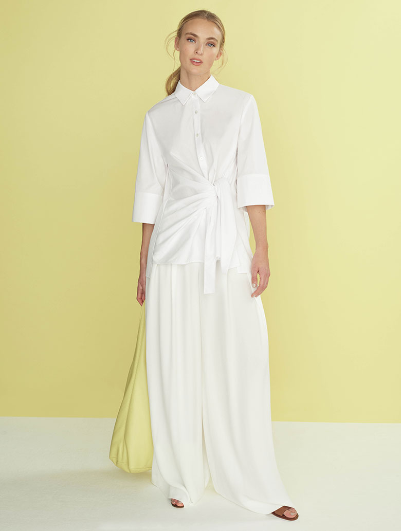 A young model dressed in an all white outfit with a white shirt and white wide leg pants. Image by Hobbs.