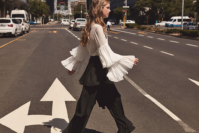 This is one serious style statement white shirt with fluffs on the sleeves. Combined with black wide leg pants that also have fluffs, looking gorgeous. Image by Girls on Film.