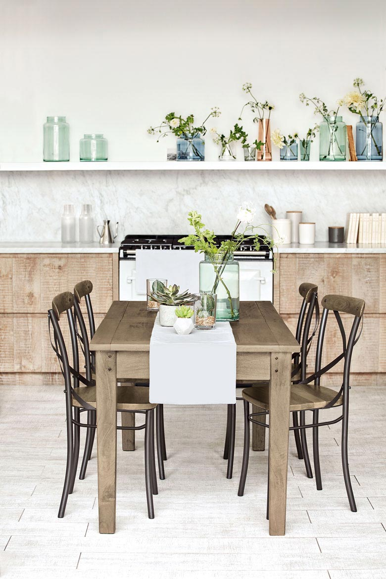 A minimal contemporary kitchen in the background makes a great contrast to a more rustic dining setting in the foreground. Image by M&S.