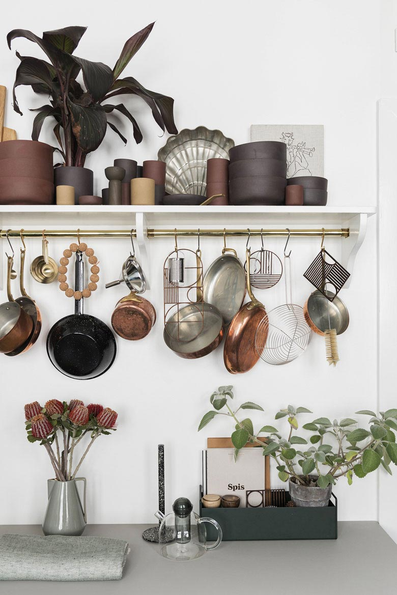 A good looking cluttered corner with all those pots and pans hanging from the white kitchen shelf. But a small planter is always a great addition. Image by Nest.co.uk.