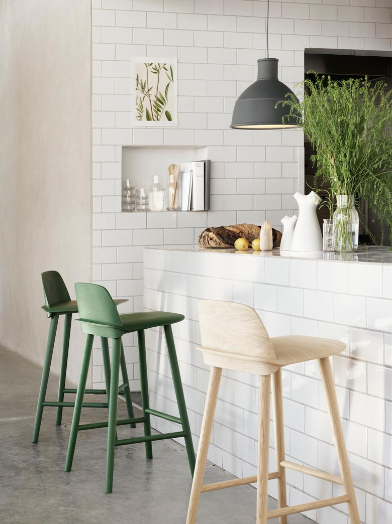These cool bar stool chairs in various colors look ideal for this tall white kitchen counter. Image by Nest.co.uk.