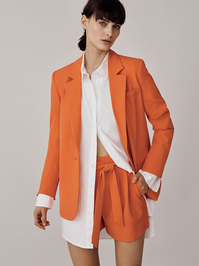 A white oversized shirt looks really edgy when orange blazer and orange paperbag shorts. Image by Oasis.