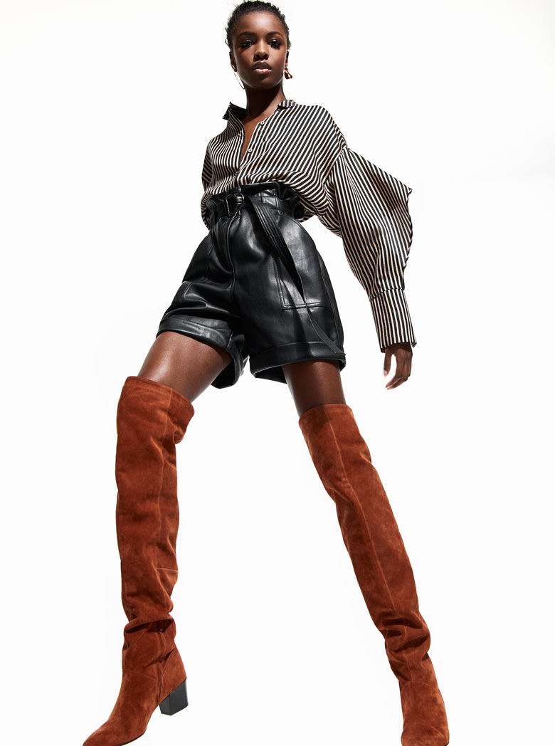 Black leather high waisted shorts worn with knee high boots, are ideal for spring. This young model wears them with a shirt and a sexy attitude. Image by River Island.