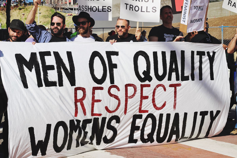 Men holding a large banner during a march saying men of quality respect womens equality
