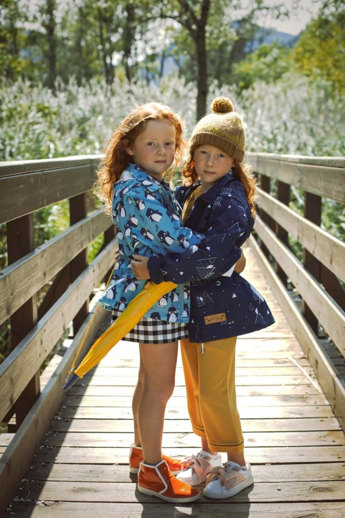 Two twin sisters looking pretty in raincoats embracing each other on a narrow timber footbridge outdoors.
