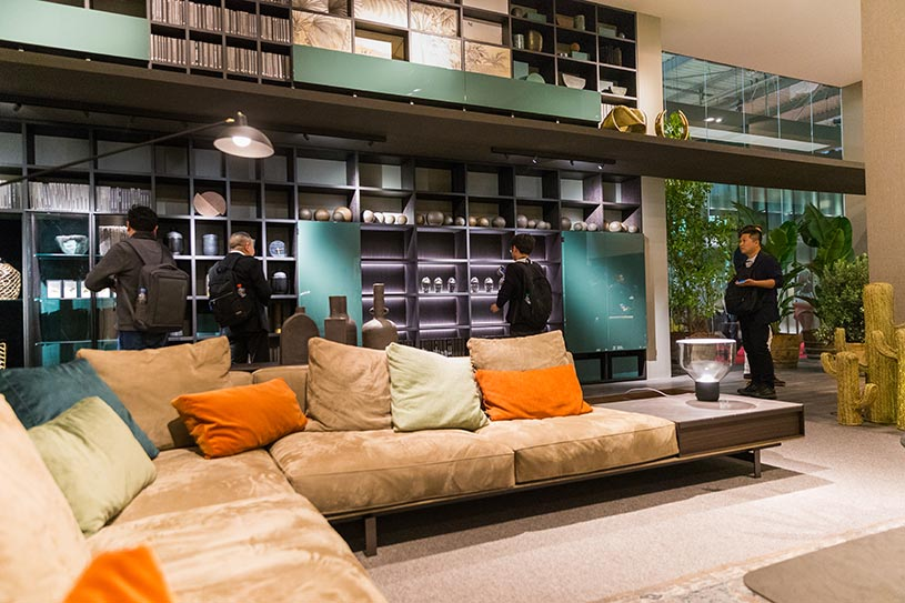 A living room setup with a modular beige sofa and a tall bookcase, both with color accents. Image by Luca Fiammenghi from the Lema stand at Milan's Furniture Fair.