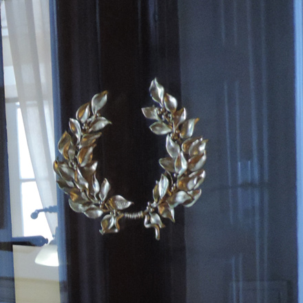 A silver wreath on a glass door found in a luxury hotel in Syros.