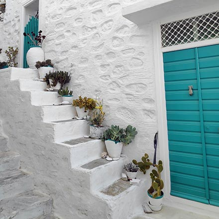 A white washed house facade with a small staircase and a turquoise front door, found in Ano Syros. Image by Velvet.