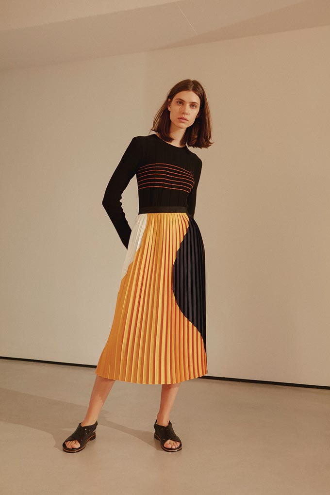 A young model wears a dark top with a colorblocked pleat long skirt. The colors of the skirt yellow, white and black make a stunning statement. Image by Jigsaw.