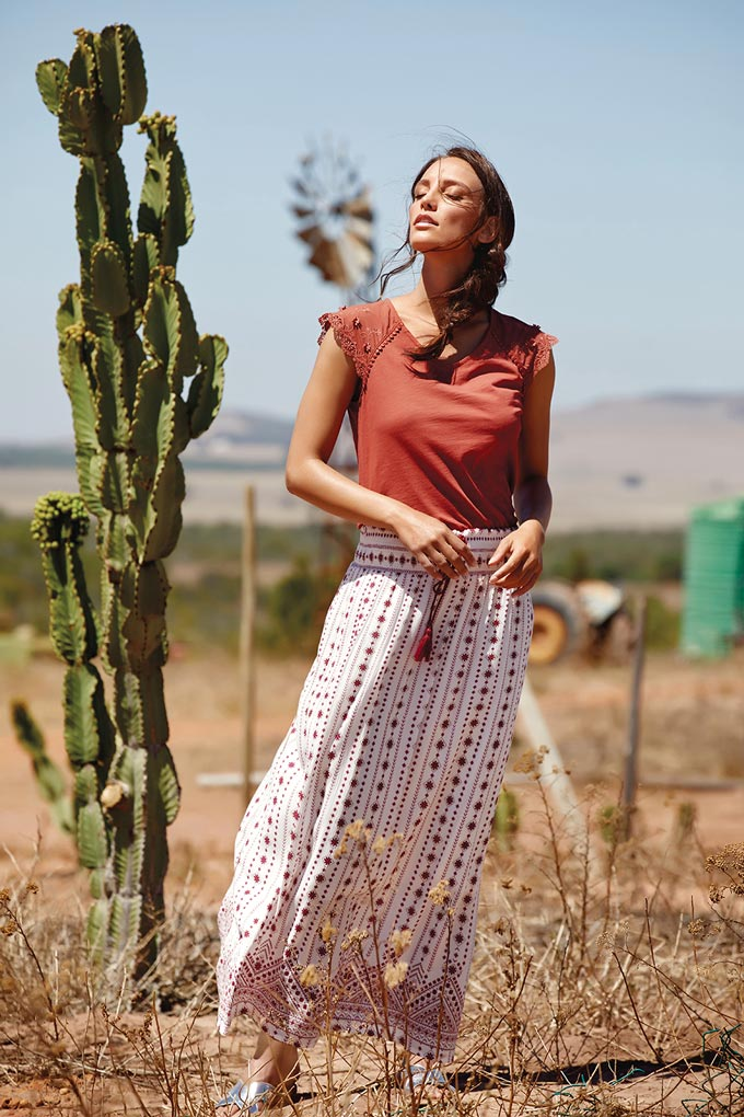 A beautiful boho white long skirt combined with a coral red top looks great on this model who's standing in a dessert. Image by M and Co.
