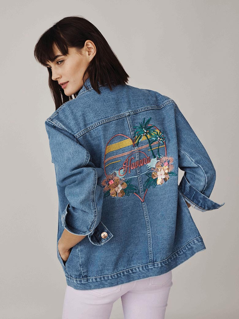 A cool denim jacket is always a must. A little embroidery at the back like in this jacket worn by a beautiful model paired with white pair of jeans. Image by Oasis stores.