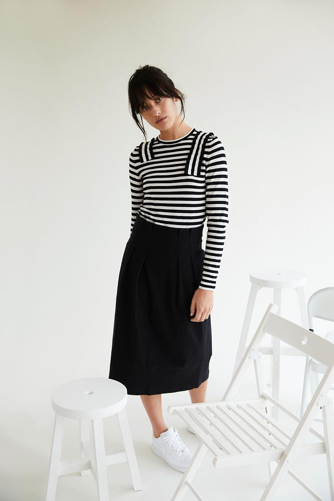 A black long A line skirt can look interesting if combined with a black and white stripe long sleeve tee and white sneakers like this model does. Image by Oliver Bonas.