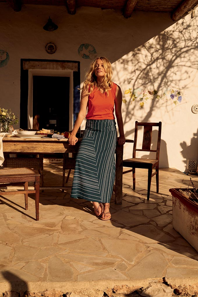 A blonde young woman wears a coral red top and a long skirt with a geometric pattern - a beautiful boho style. Image by White Stuff.