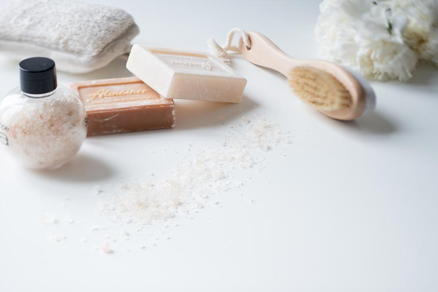 Natural soap bars, bath brush and salts styled nicely.