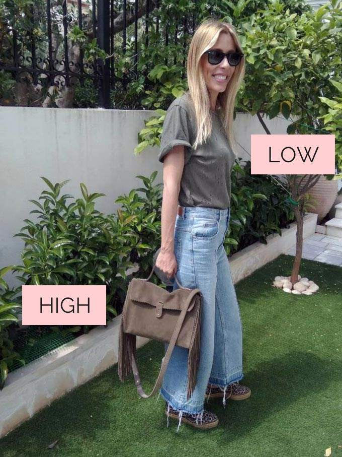 Elisabeth in a sage green tee shirt, wide leg jeans, holding a suede sage green bag with a fringe and sneakers with a leopard print. The tee is a low key staple. The fringed bag is high key staple.