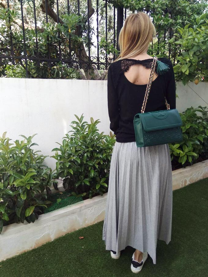 The rear view of Elisabeth whose wearing a black sweater with a statement cut at the back, a green bag, a gray maxi plea skirt and white sneakers.