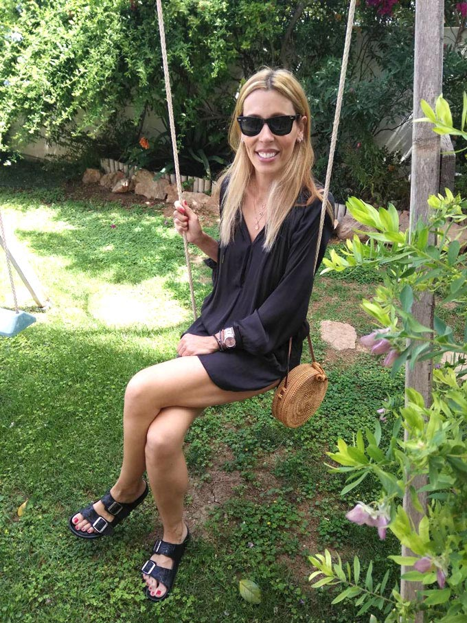 Elisabeth sitting on a swing, wearing a black mini shear dress, a round straw basket for a bag, both high key staples, and Birkenstock sandals as a low key staple with a garden in the background.