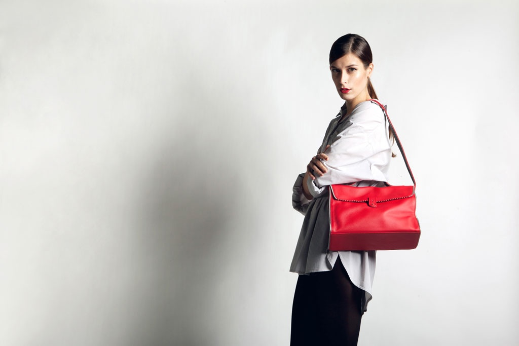A beautiful young model wearing a large red RIEN bag.