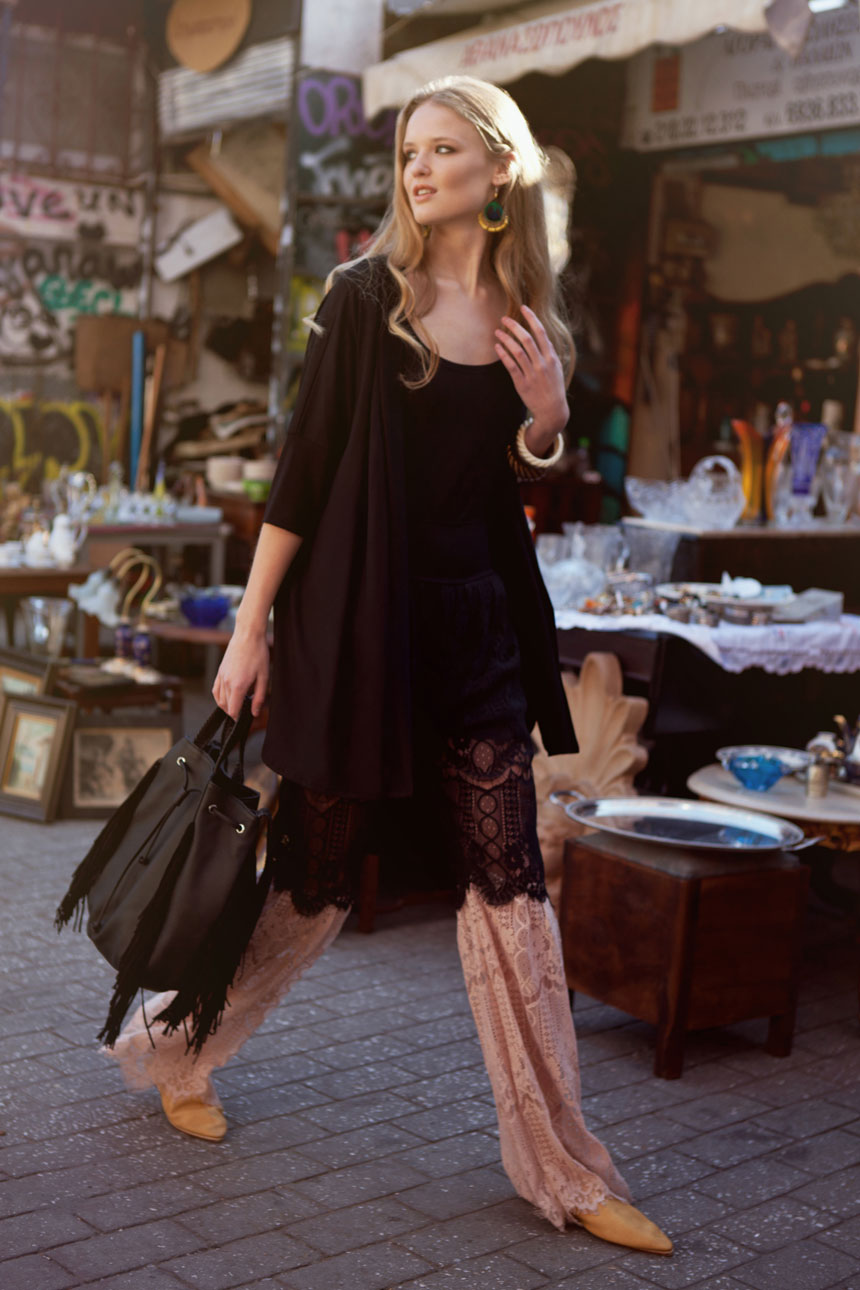 A beautiful young model wearing a black top with a pair of wide leg pants with lace, whose carrying a black leather bag is walking through a flea market looking gorgeous. All creations of RIEN by Penny Vomva.