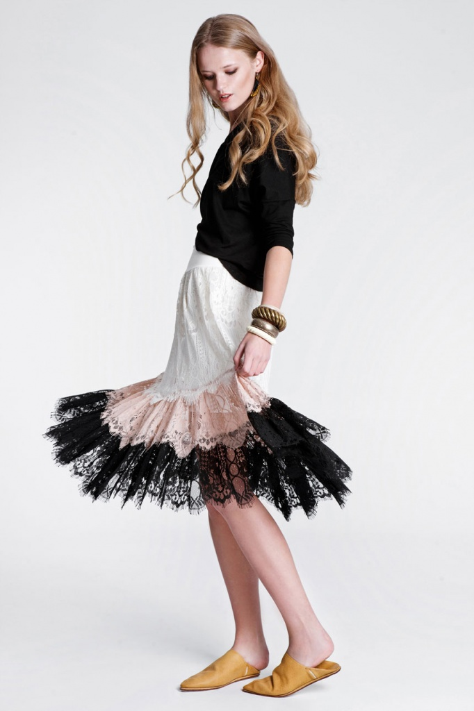 A young model wearing a black top with a white skirt with blush pink and black lace as details. Creation of RIEN.