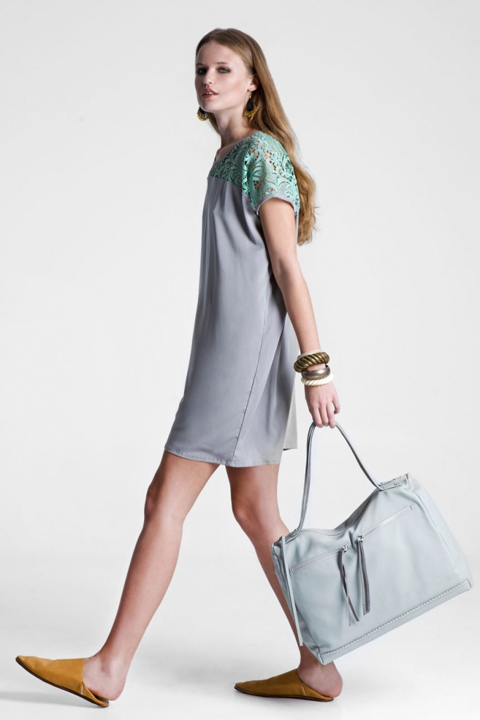 A young model wearing a short summer dress in a light purple color with short lace green sleeves, carrying a light purple big leather bag. All creations of RIEN.