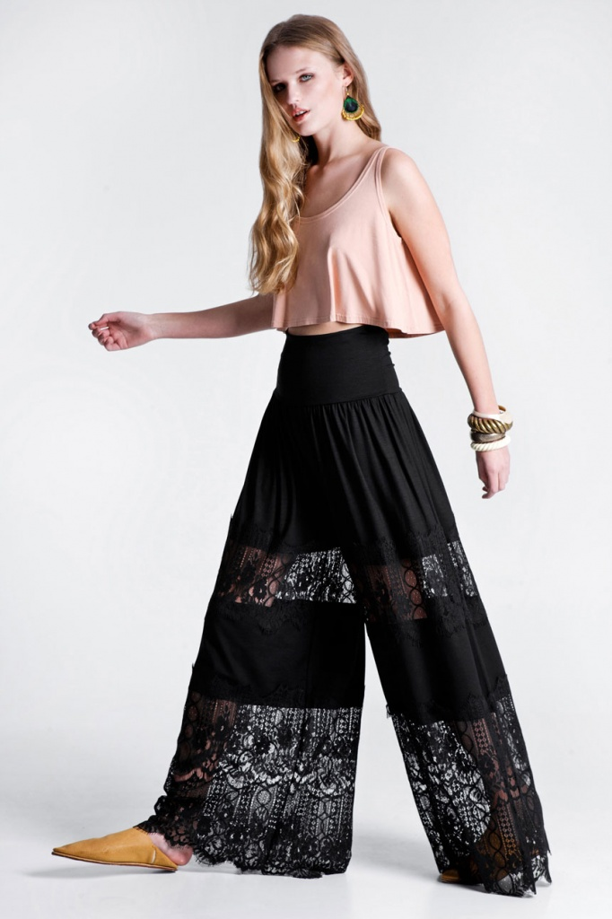 A beautiful young model wearing a soft peach tango top and a pair of black wide leg lace pants. All creations of RIEN.