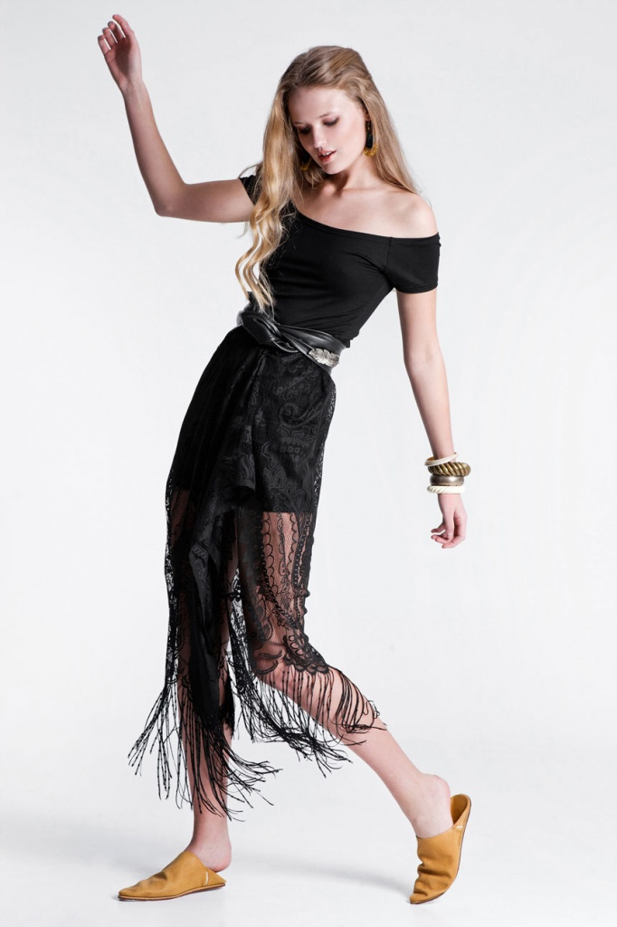 A young model wearing a black Bardot top with a black lace skirt. All creations of RIEN.