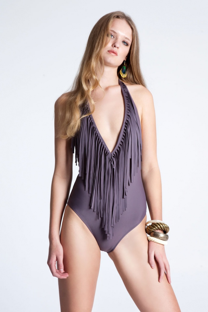 A one piece muted purple RIEN swimsuit with a deep v neckline and a fringe, worn by a young beautiful model.
