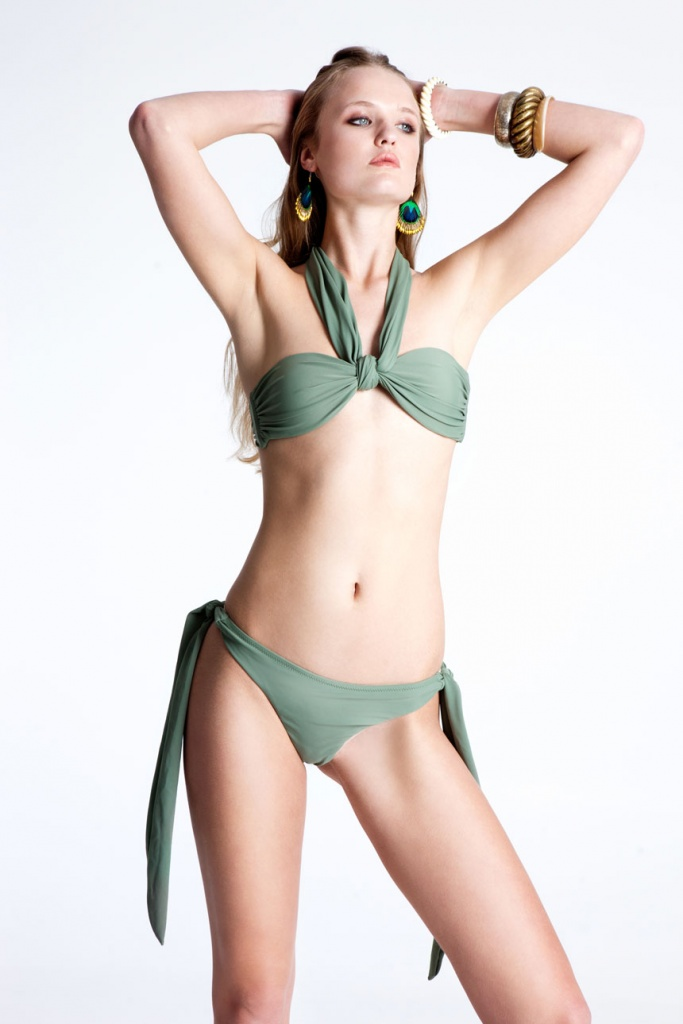 A RIEN bikini in a muted sage green worn by a beautiful young model.