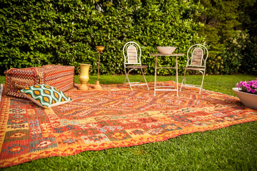 An outdoor setup in a garden with an area kilim rug, throw pillows and wooden garden furniture.