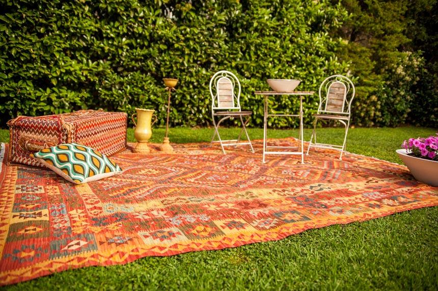 An outdoor setup in a garden with an area kilim rug, throw pillows and wooden garden furniture.