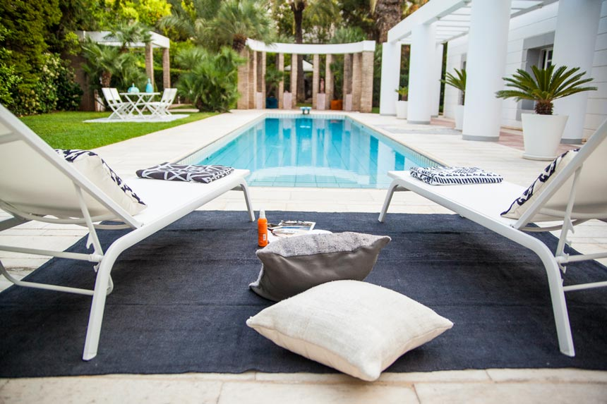 A blue jute rug with two white sunbeds atop by a pool and a garden.
