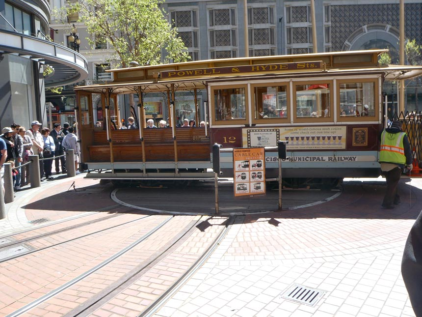 An old cable car taking a turn at a terminal at San Francisco, under the watchful eyes of tourists.