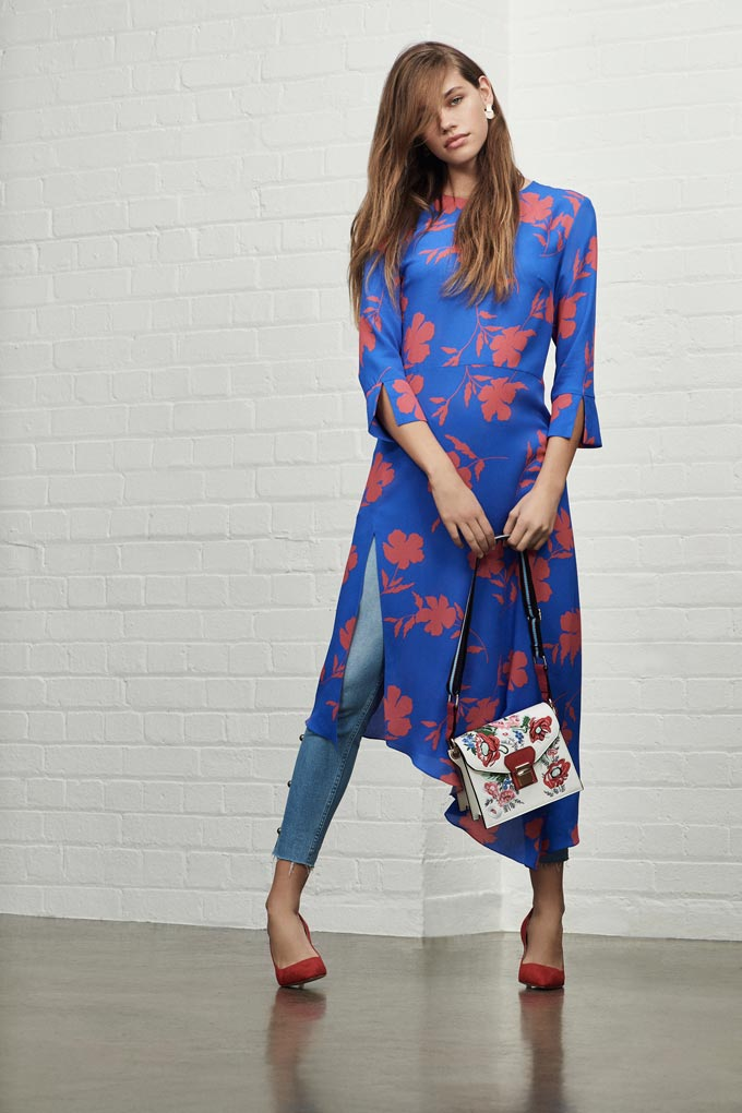 A young woman wearing a bright blue with a pink floral print dress over a pair of jeans paired with red pumps. Image by Debenhams.