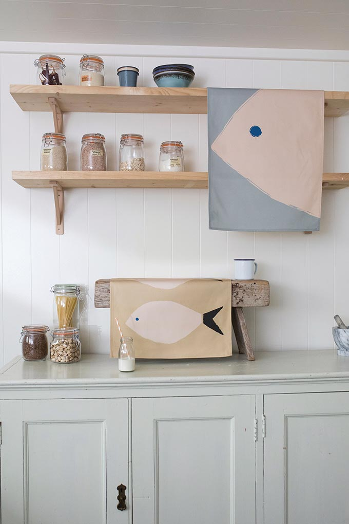 What a nice detail. A soft blush pink fish print on tea towels hanging from the wooden racks in a kitchen. Image by Anorak.