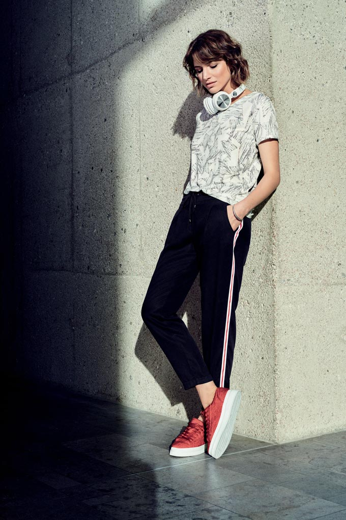 A stylish athleisure wear. A tee worn by a young woman over a pair of black track pants and red sneakers. Image by Betty and Co.