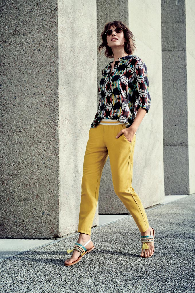 A woman dressed in style with a high key blouse, yellow low key pants and high key flat sandals with tassels. Image by Betty & Co.