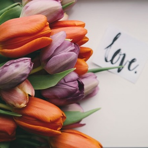 A bouquet of orange and purple tulips flat on a white surface with a note that reads love.