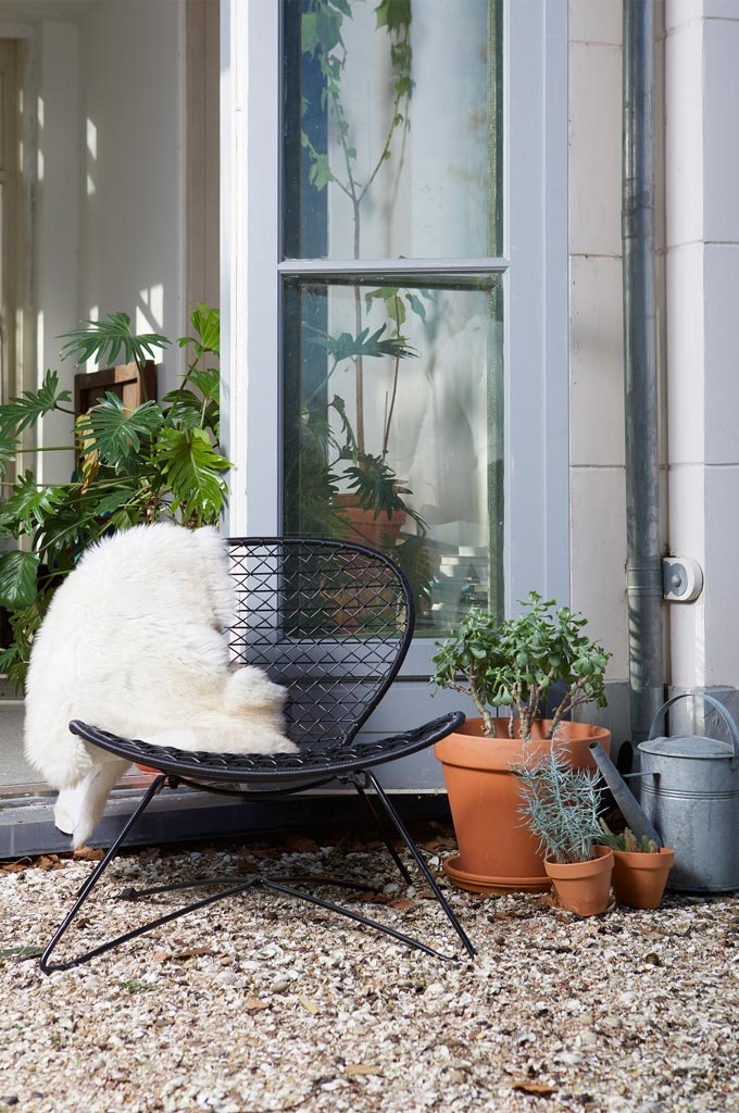 A black wire outdoor chair with a white sheepskin on top can form a nice little nook next to the clay plant pots. Image by Cuckooland.