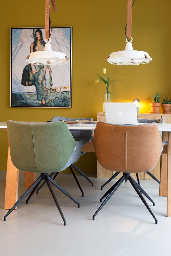 A dining setup against a mustard yellow accent wall with a large artwork, two designer pendant lights and two different colored beautiful chairs. Image by Cuckooland.