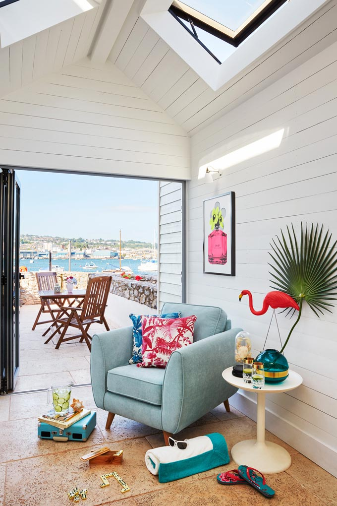 A peak at a beach home from a sitting room with a blue armchair and white round side table and an outdoor dining setup in the terrace outside in the background. Pops of vibrant color have really given a more modern and edgy look at this coastal home. Image by DFS Furniture.