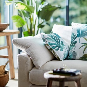 How jungalicious is this? An off white sofa with tropical leaves print throw pillows and lots of lush, green foliage in the background. Image by DFS Furniture.
